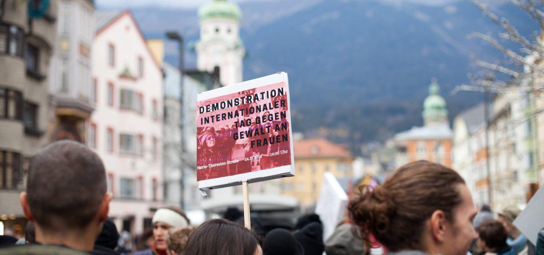 Demoschild mit der Aufschrift: Demonstration Internationaler Tag gegen Gewalt an Frauen. Im Hintergrund die Nordkette und Marien-Theresienstraße.