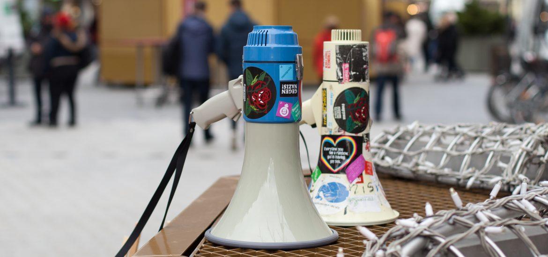 Bild von zwei Megaphonen mit bunten Stickern darauf. Im Hintergrund lässt sich eine belebte Straße erkennen.